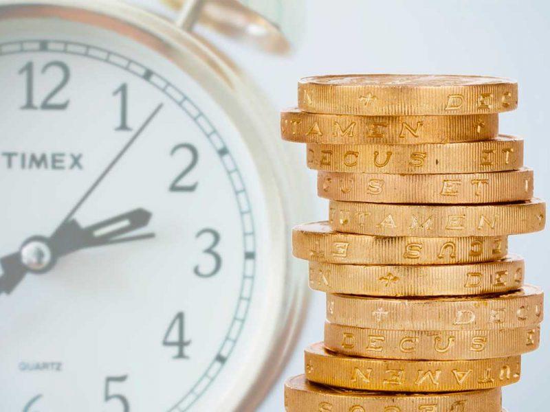 Relógio ao fundo e moedas douradas