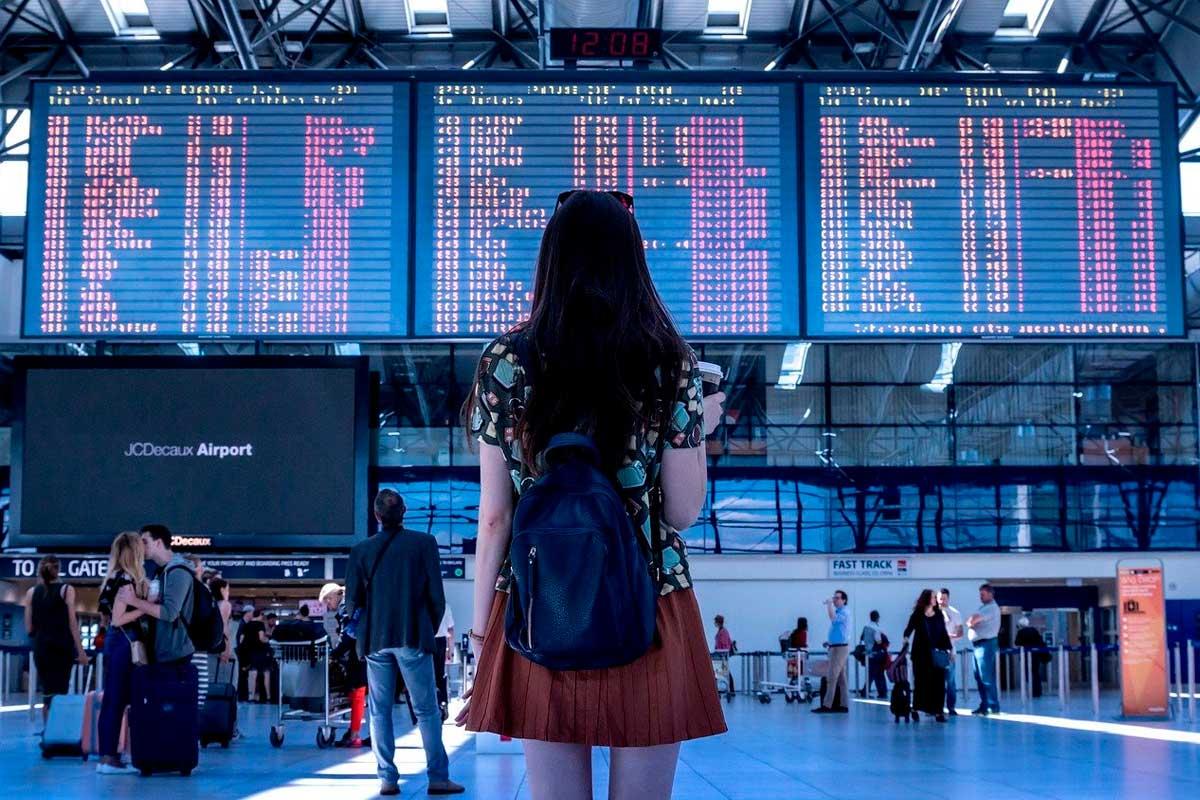 Mulher lendo destinos de voos em telas dentro de um aeroporto