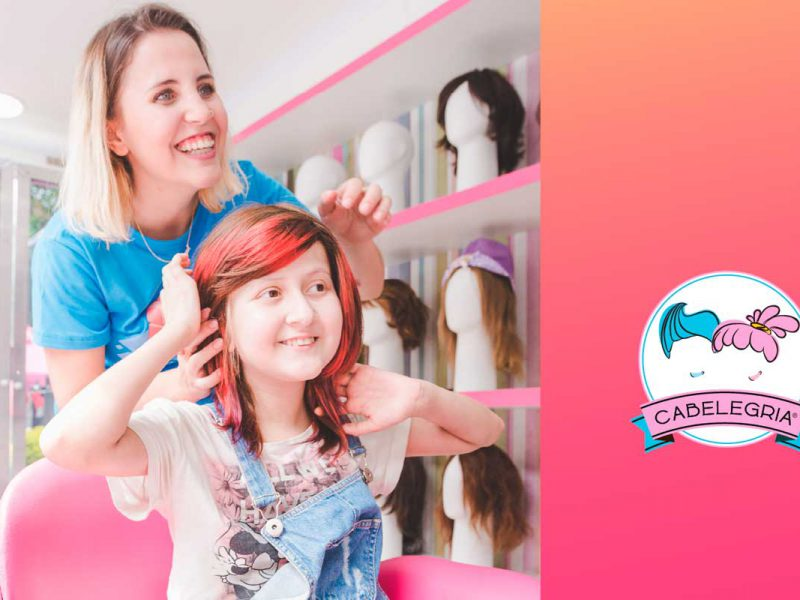 Mulher colocando peruca em menina sorridente