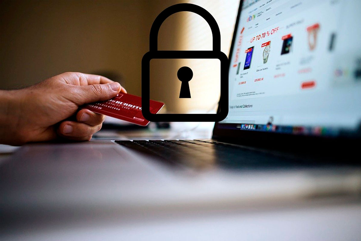 Mão com cartão de crédito simulando compra em compudador