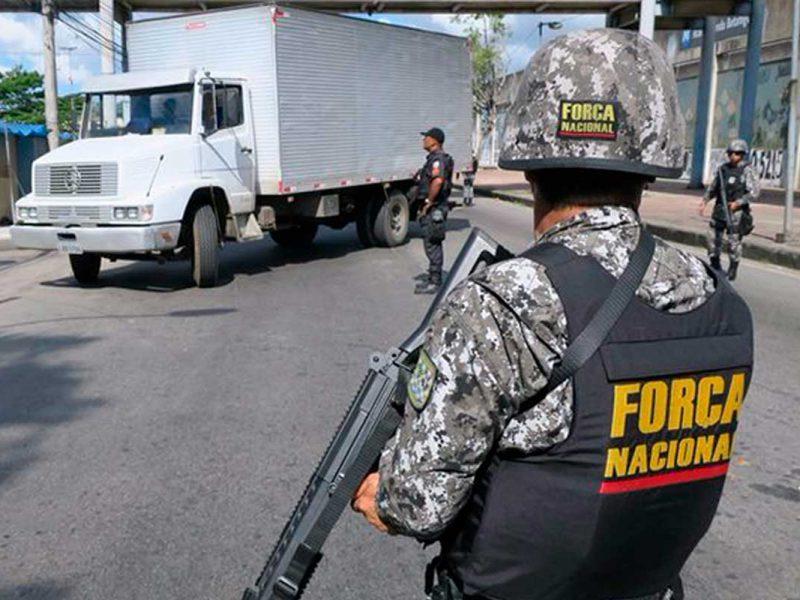 Millitar da Força Nacional interditando uma rua