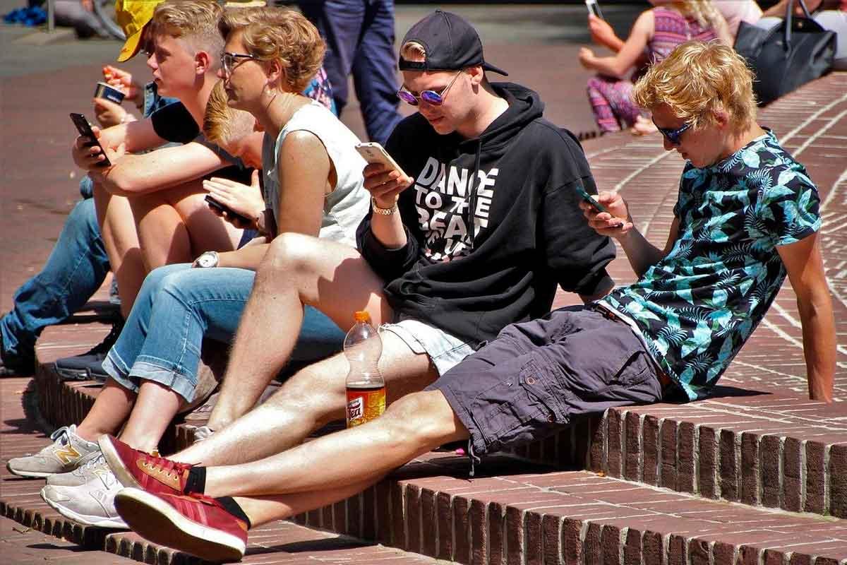 Jovens com celular na praça