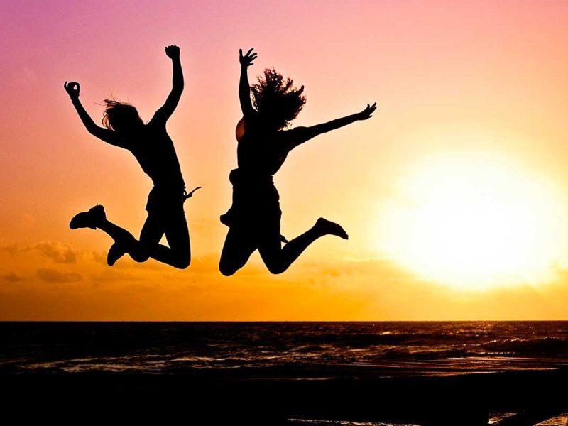 Duas mulheres saldando com por do sol no fundo - Liberdade