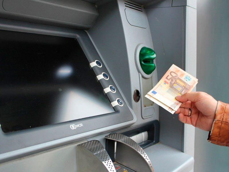Pessoa fazendo saque em euro de um caixa automático