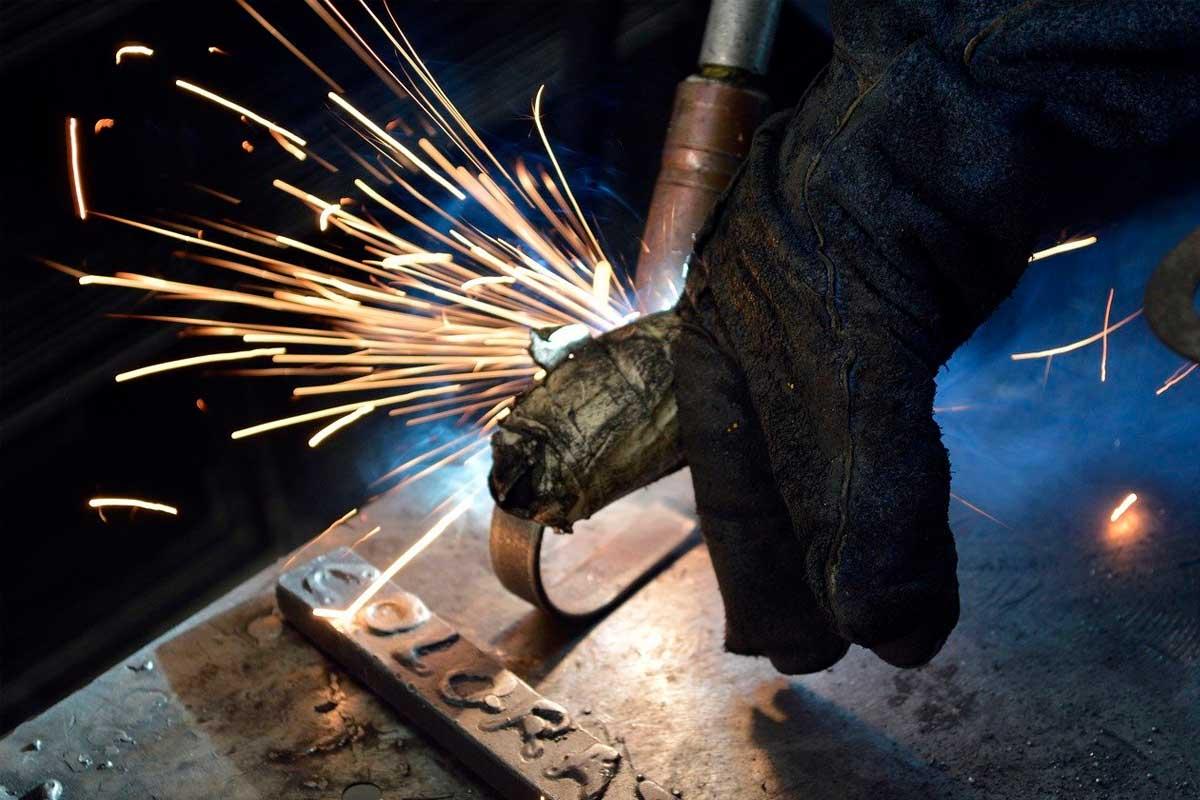 Homem manipulando ferramentas e aço