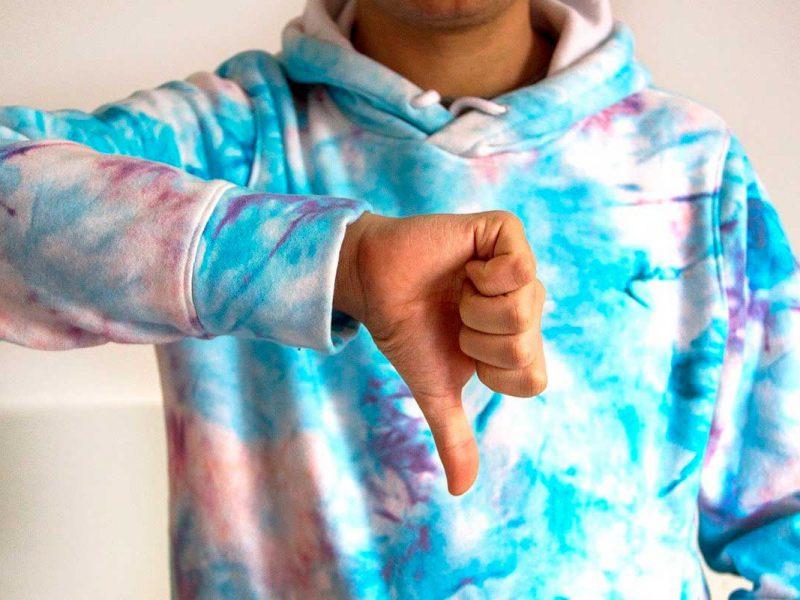Pessoa com sinal de polegar para baixo demonstrando insatisfação